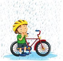 Jongens berijdende fiets in regen