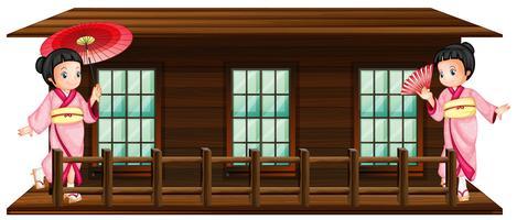 Twee Japanse meisjes bij houten hut