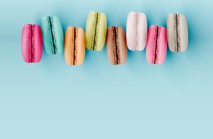 Hoog gedetailleerde kleurrijke macarons op blauwe achtergrond, vectorillustratie