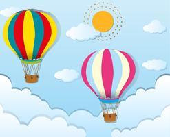 Twee ballons die in blauwe hemel vliegen