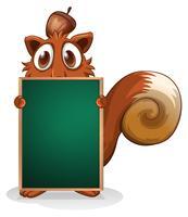 Een eekhoorn die zich aan de achterkant van een leeg schoolbord verbergt