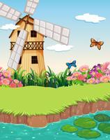 Een barnhouse met een windmolen dichtbij de rivier