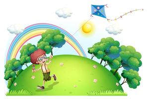Een jongen speelt met zijn vlieger op de heuveltop