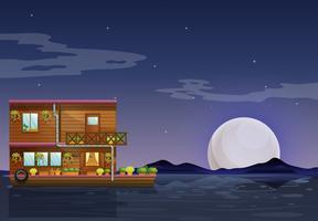 Een botenhuis dat midden in de nacht drijft
