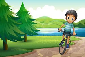Een jongen die dichtbij de pijnboombomen bij de rivieroever biking