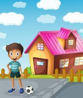 een jongen, voetbal en huis