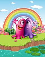 Twee monsters bij de rivieroever met een regenboog in de lucht