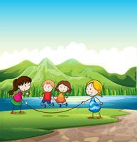 Vier kinderen spelen met een touw in de buurt van de rivier