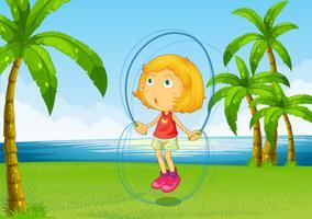 Een meisje speelt springtouw aan de rivier