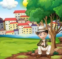 Een man zit boven de rots onder de boom