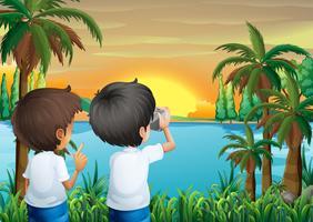 Twee kinderen met een camera aan de rivieroever