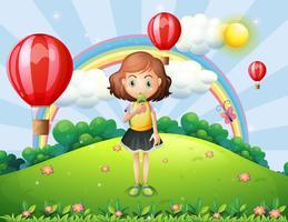 Een meisje een ijsje eten op de heuveltop met hete lucht ballonnen