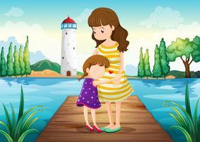 Een jong meisje dat haar moeder koestert bij de brug