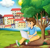 Een jonge jongen die laptop onder de boom met behulp van bij riverbank