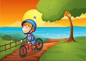 Een jonge jongen die dichtbij de rivier biking