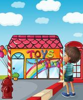 Een jongen die in de buurt van de speelgoedwinkel staat