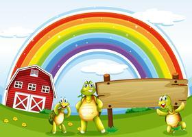 Drie schildpadden dichtbij het houten uithangbord en de regenboog
