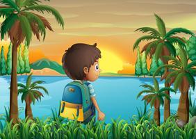 Een jongen met een tas die naar de zonsondergang kijkt