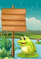 Een kikker dichtbij een leeg houten bord