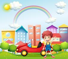 Een jongen en zijn rode auto bij de hoge gebouwen