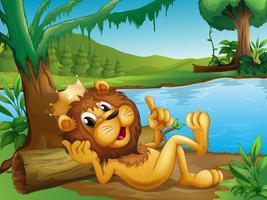 Een koningsleeuw die in een boomstam bij de rivieroever ligt