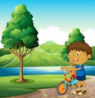Een kind aan de rivieroever speelt met zijn fiets
