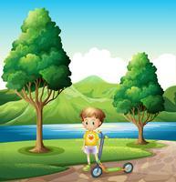 Een jonge jongen met een autoped die zich dichtbij de rivier bevindt