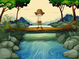 Een jongen die boven de stam bij de rivier staat