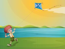 Een jonge jongen die met zijn vlieger bij riverbank speelt
