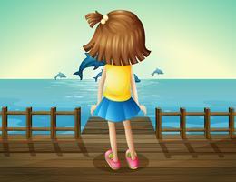 Een jong meisje kijkt naar de dolfijnen
