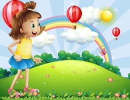 Een jong meisje op de heuvel kijkt naar de zwevende ballonnen