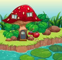 Een mier dichtbij het rode paddestoelhuis