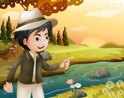 Een man met een hoed op de rivieroever