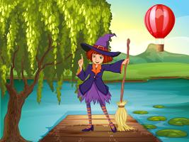 Een heks met een bezem die bij de haven staat
