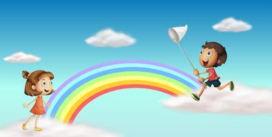 Gelukkige jonge geitjes dichtbij de kleurrijke regenboog