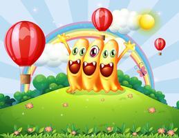 Een heuveltop met drie blije monsters die naar de zwevende ballonnen kijken