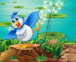 Een kleurrijke vogel boven de boomstronk dichtbij de vijver