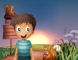 Een jonge jongen en twee eekhoorns dichtbij de lege signage en de brievenbus