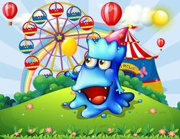Een gelukkig blauw monster op de heuveltop met een carnaval