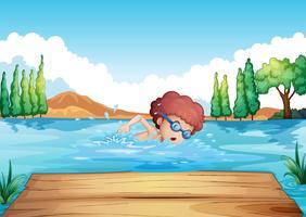 Een jongen die dichtbij de duikplank zwemt