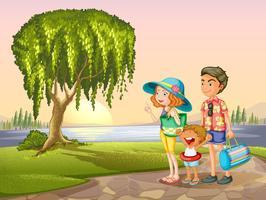man, vrouw en kind staan rond de boom
