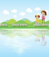 Een jongen en een meisje die naar het meer kijken