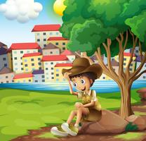 Een jonge ontdekkingsreiziger die boven de rots over de hoge gebouwen zit