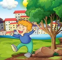 Een gelukkige jonge jongen dichtbij de boom