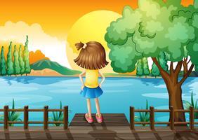 Een meisje dat bevindt zich onder ogen ziend bij de rivier