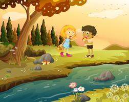 Een jongen en een meisje spelen in het bos in de buurt van de rivieroever