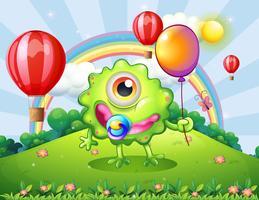 Een baby groen monster op de heuveltop met een regenboog vector