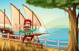 Een houthakker in de buurt van het hek aan de rivieroever met een schip