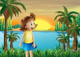 Een klein meisje op de oever van de rivier