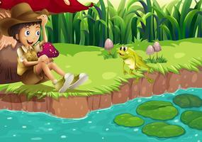Een jongen en een kikker aan de rivieroever